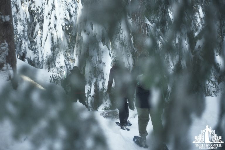 3 people snowshoeing partially obscured by trees on Cypress Mountain in Vancouver