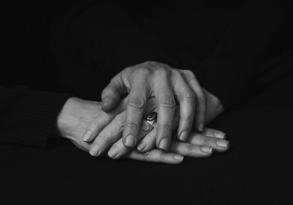 Black and white photo of a woman holding her elderly mothers hand between her own during a mother and daughter session by by Vancouver contemporary portrait photographer Angela McConnell