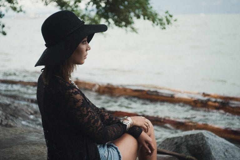 Natural light portrait of a young woman in a black hat sitting on a rock under a tree looking out over English Bay