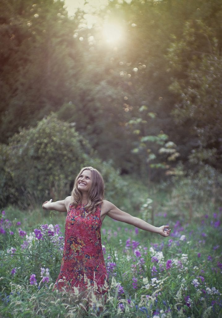 Natural light image of a young woman with outstretched arms in a field of wildflowers backlit by the setting sun by Vancouver contemporary portrait photographer Angela McConnell