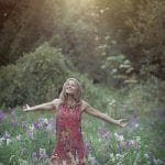 Natural light portrait of young woman with outstretched arms in a field of wildflowers backlit by the setting sun