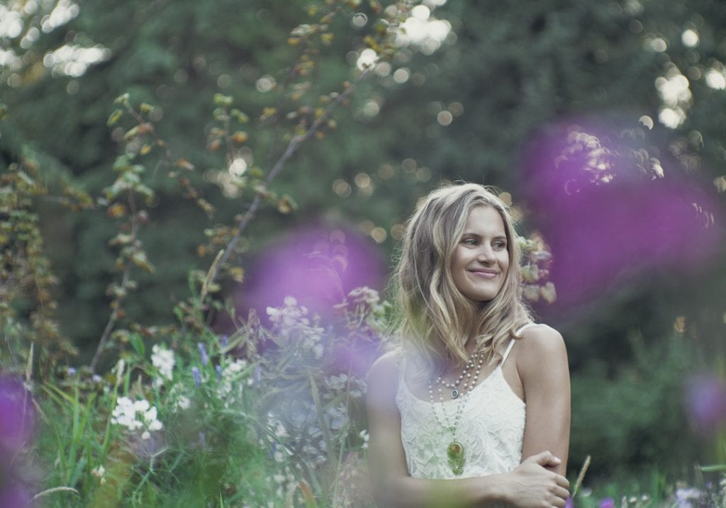 Natural light portrait of a young woman posing in a field of wildflowers