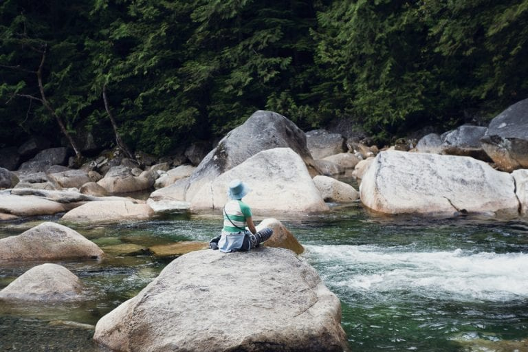 Image of a woman sitting on a boulder overlooking a river and waterfall at Golden Ears Provincial Park