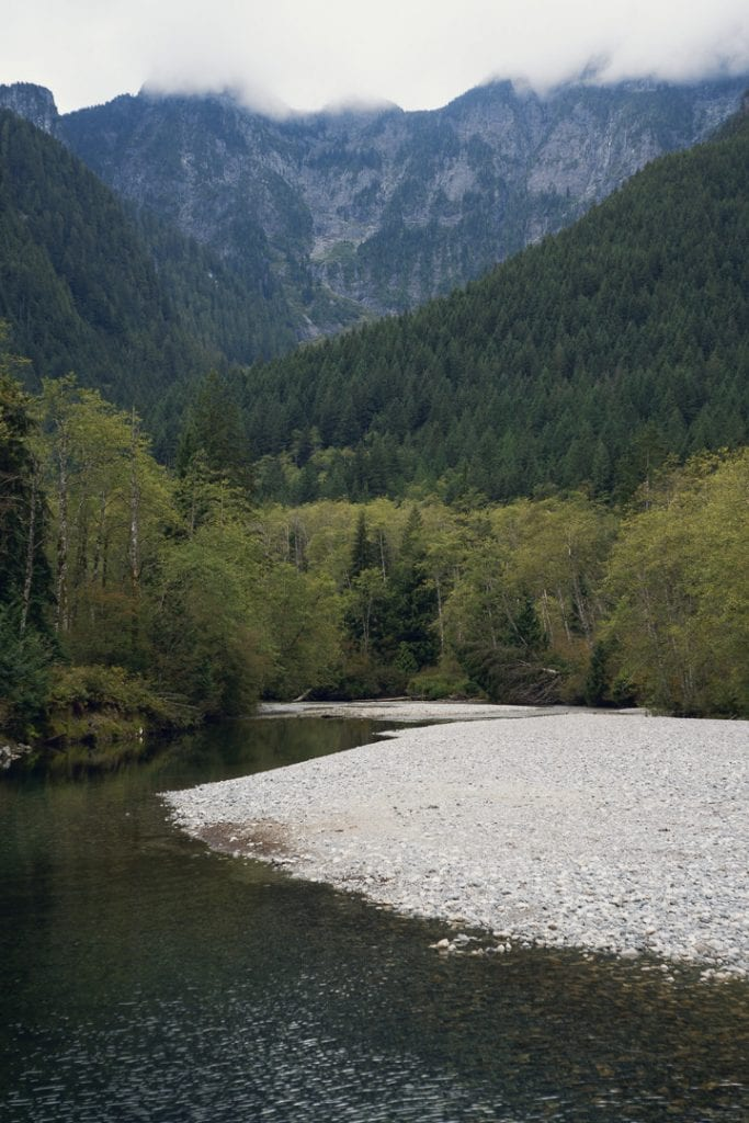 Landscape image of a river with cloud covered mountain range in the background at Golden Ears Provincial Park