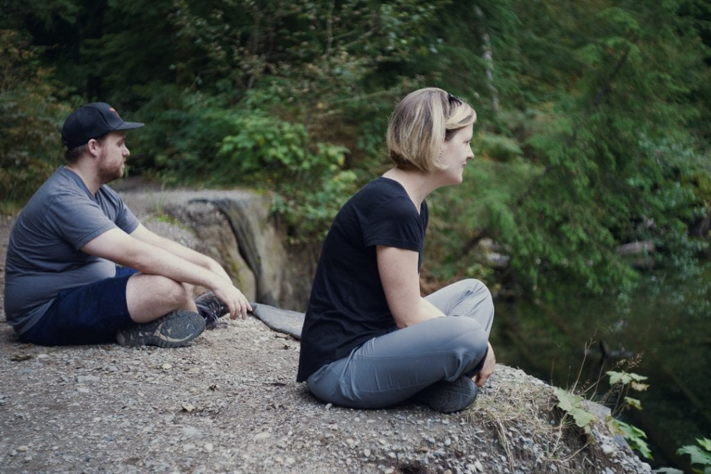 Image of a man and woman sitting looking over a river while camping at Golden Ears Provincial Park