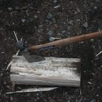 Image of an axe in a log in a campground
