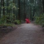 Natural light portrait of a young woman wearing a flower crown twirling chiffon around her amongst the forest at Pacific Spirit National Park in Vancouver BC