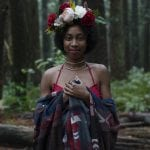 Natural light portrait of a young woman wearing a flower crown smiling at the camera while in the forest at Pacific Spirit National Park