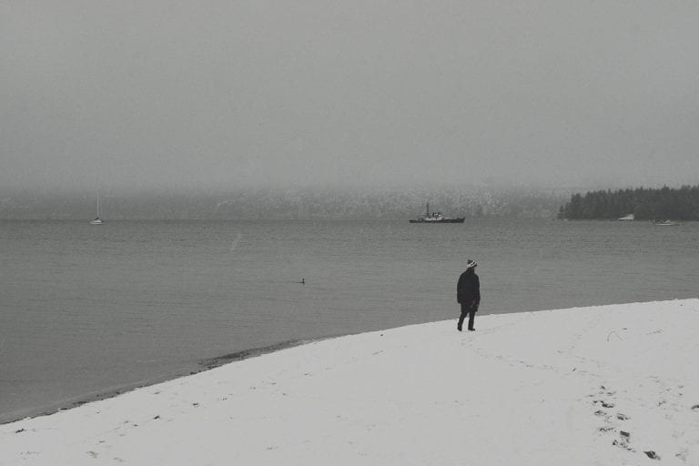 Kitsilano winter wonderland with a person walking along the beach with West Vancouver and Stanley Park in the background on a snowy day in Vancouver BC