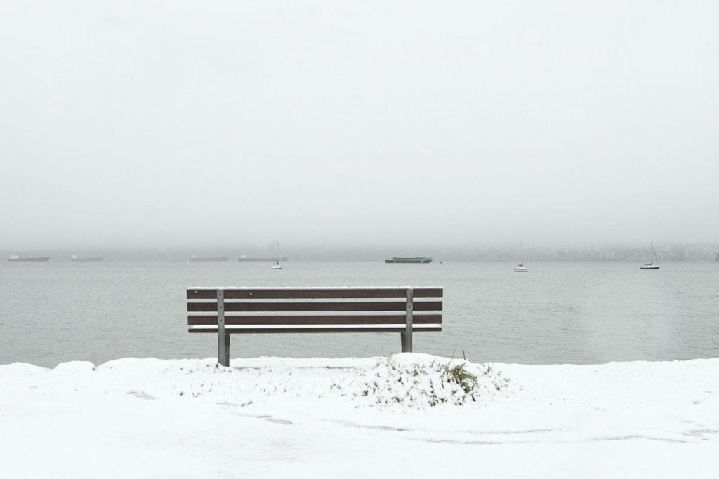 Park bench overlooking the water at Kitsilano Yacht Club looking towards West Vancouver on a snowy day in Vancouver BC