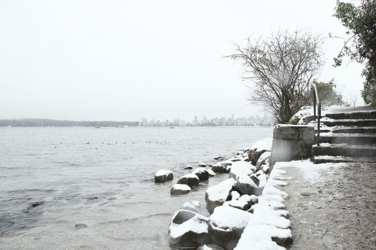 Snow on the footpath and rocks at Point Grey Park looking across to English Bay on a snowy day in Kitsilano