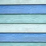 Coloured weatherboard cladding on boathouses on the coast at Pauatahanui Inlet in Wellington