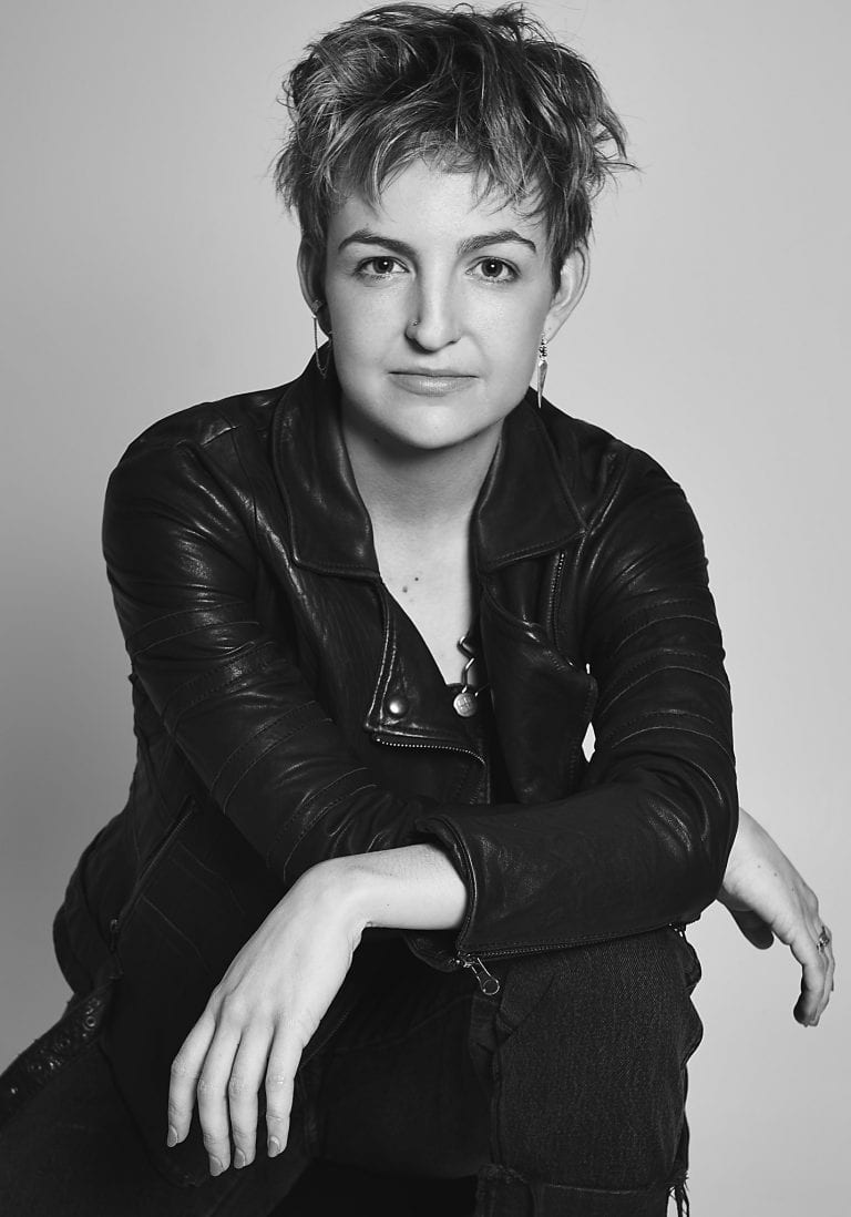 Black and white portrait of an aussie actress wearing a black bralette, jeans and leather biker jacket by Vancouver contemporary portrait photographer Angela McConnell