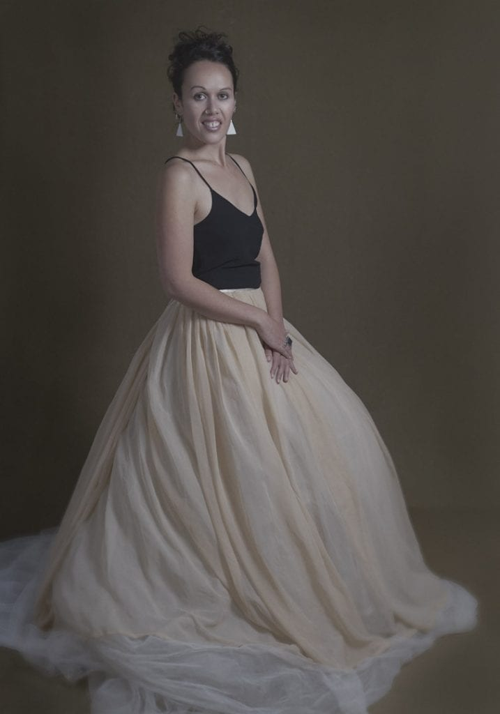 Studio portrait of a young Maori woman in a large tulle skirt looking and smiling at the camera during a session where kiwi expats come together by Vancouver contemporary portrait photographer Angela McConnell