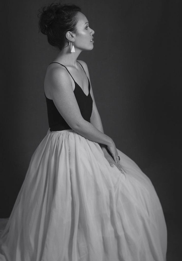Black and white studio portrait of a young Maori woman in a large tulle skirt posing in profile during a session where kiwi expats come together by Vancouver contemporary portrait photographer Angela McConnell