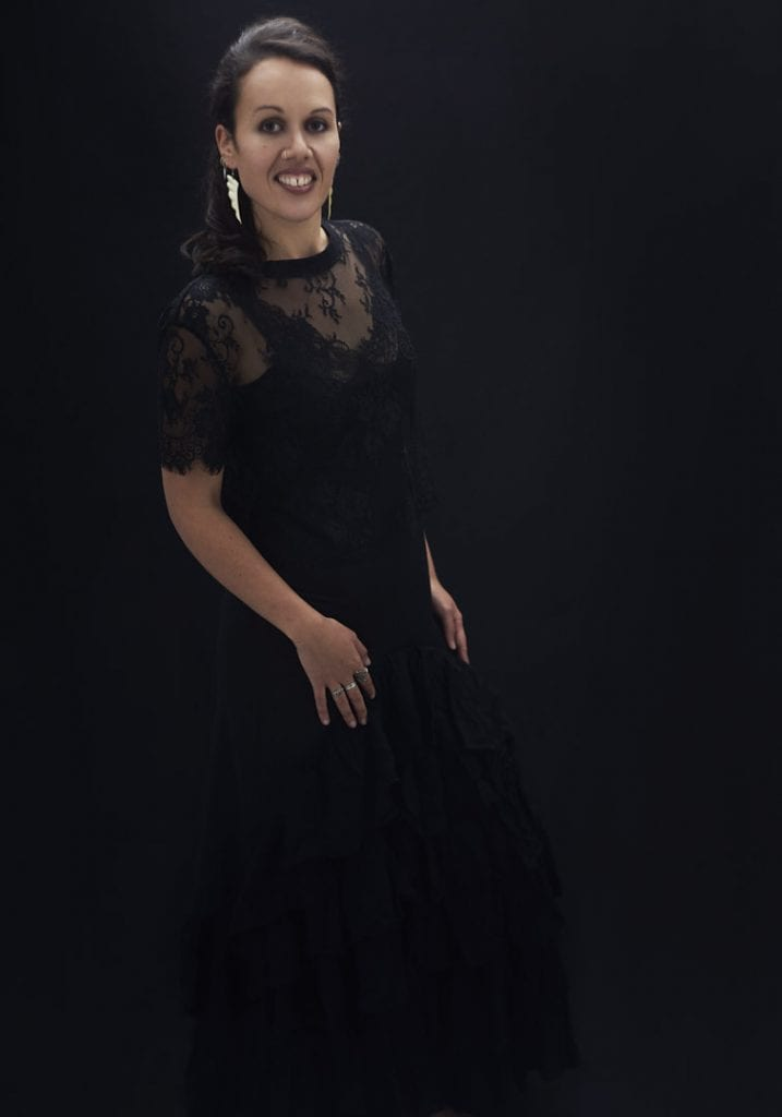Studio portrait of a young Maori woman in a black dress and lace top smiling at the camera during a session where kiwi expats come together by Vancouver contemporary portrait photographer Angela McConnell
