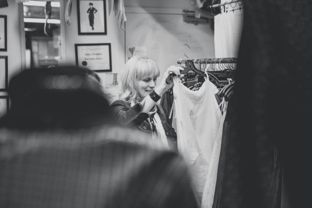 Black and white image of a woman partially obscured looking at clothing on a hanger at a pop up design event