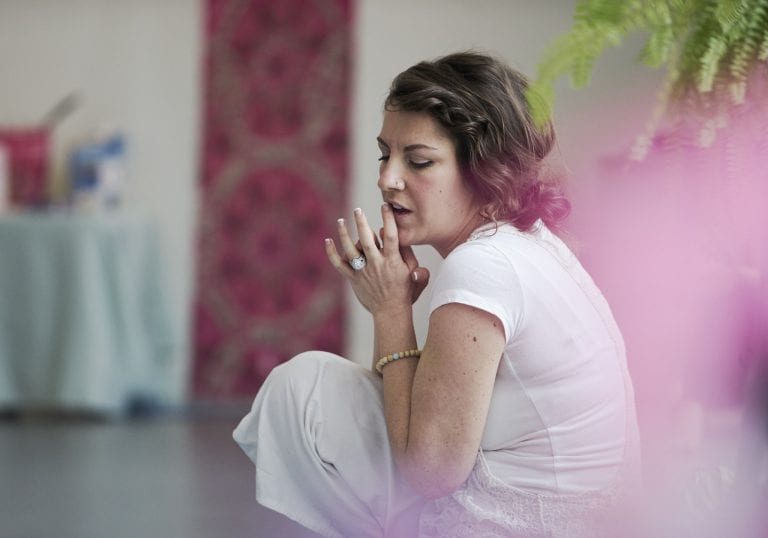 A woman dressed in white sitting on a yoga mat directing a group of women at a mother and daughter retreat in Vancouver focusing on relationships and self care by Vancouver workshop and retreat photographer Angela McConnell