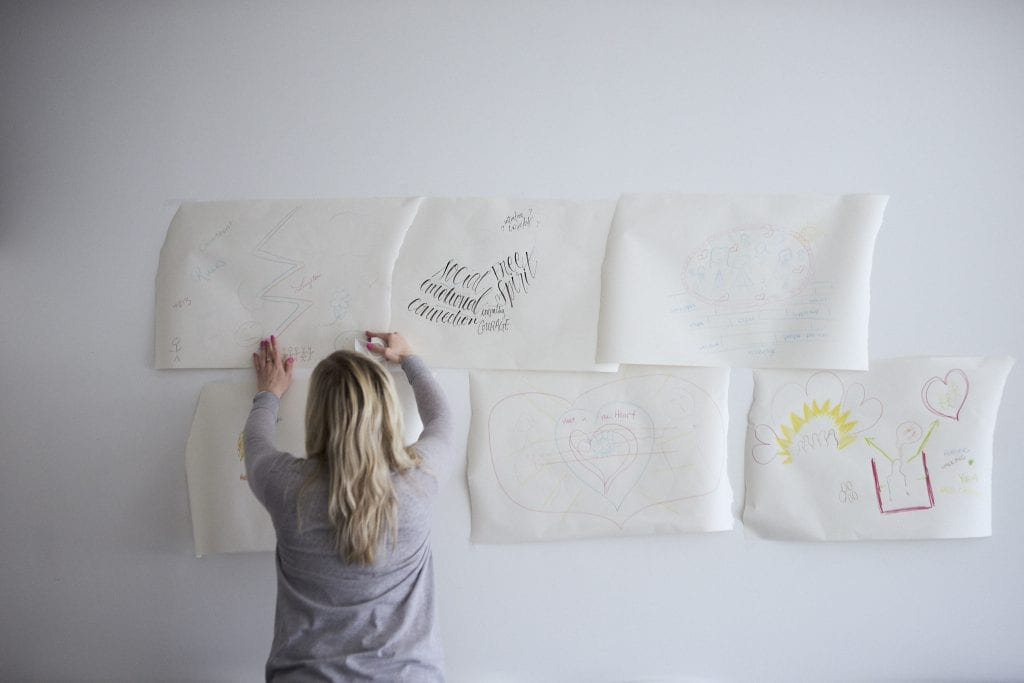 A blonde woman tapes pieces of paper to a wall during an exercise at a meeting by Vancouver workshop and retreat photographer Angela McConnell