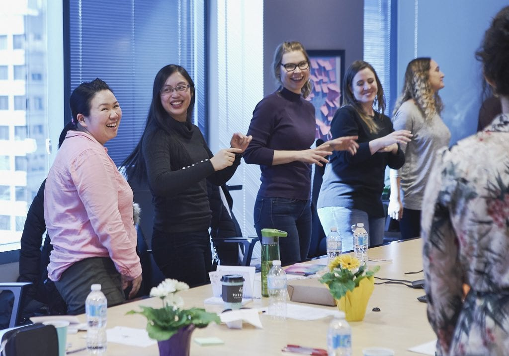 Image of a group of women laughing and dancing during a self care workshop in Vancouver