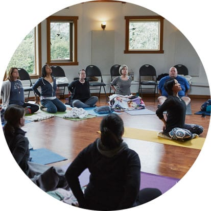 A yoga instructor sits in the middle of a room demonstrating a heart opening pose while leading a yoga session at a self care for educators workshop at Roundhouse Farm, Victoria BC by Vancouver workshop and retreat photographer Angela McConnell