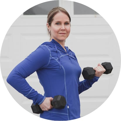 Outdoor portrait of a personal trainer wearing a purple sweatshirt holding weights by Vancouver business portrait and branding photographer Angela McConnell