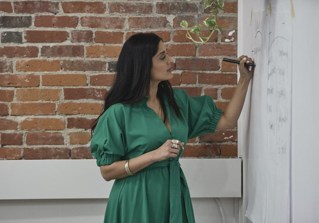 Workshop facilitator in an emerald green dress and long dark hair writing on a piece of paper stuck to the wall at a self care and confidence workshop by Vancouver workshop and retreat photographer Angela McConnell