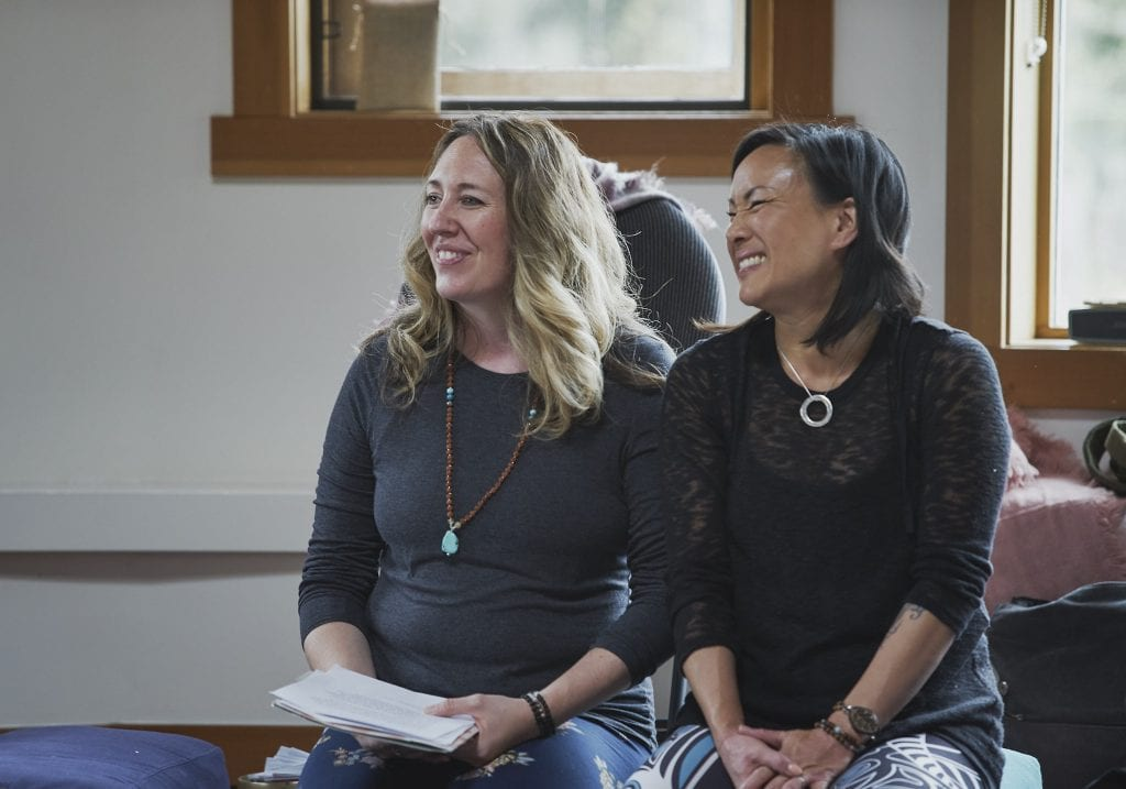 A workshop facilitator and yoga instructor smile at attendees during an introduction at a self care for educators workshop at Roundhouse Farm, Victoria BC by Vancouver workshop and retreat photographer Angela McConnell