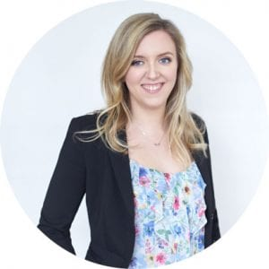 Image of a smiling woman with blonde hair wear a floral shirt under a blue blazer by Vancouver business portrait and branding photographer Angela McConnell