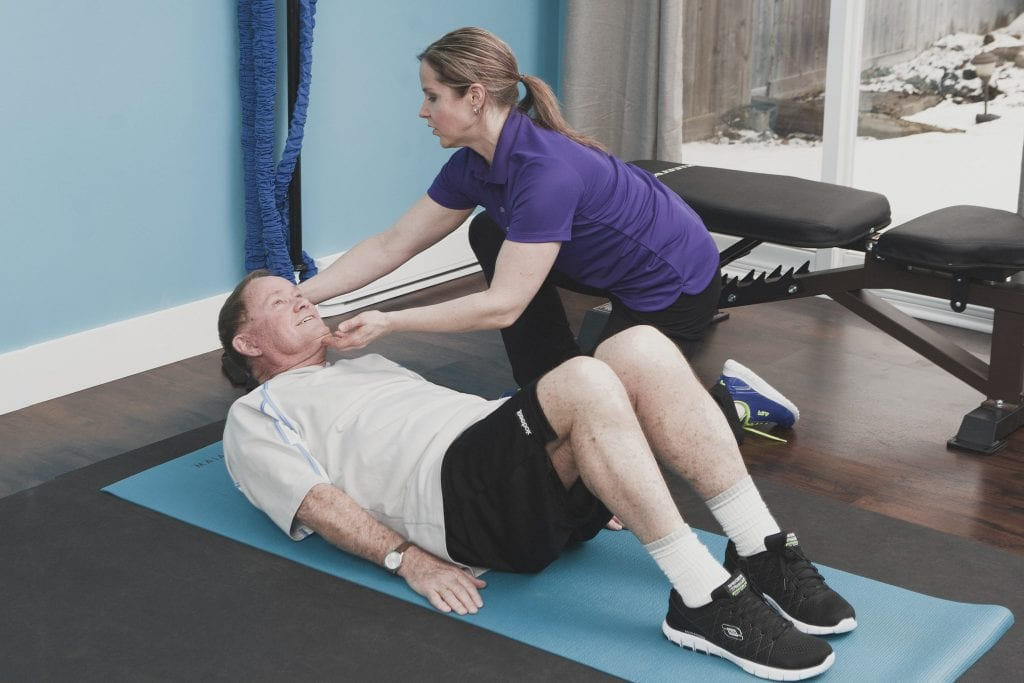 Image of a personal trainer demonstrating correct technique during a session with an elderly client by Vancouver business portrait and branding photographer Angela McConnell