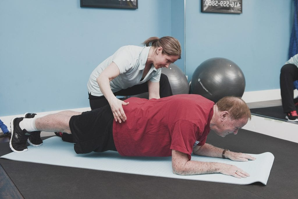 Image of a personal trainer demonstrating correct planking form during a session with an elderly client by Vancouver business portrait and branding photographer Angela McConnell