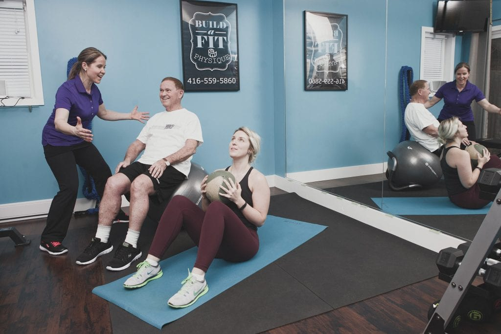 Image of a personal trainer helping clients during a session in their studio by Vancouver business portrait and branding photographer Angela McConnell