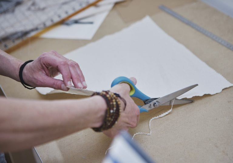Pinking shears are used to trim the edges of a linen square in preparation for making a product by Vancouver business portrait and branding photographer Angela McConnell