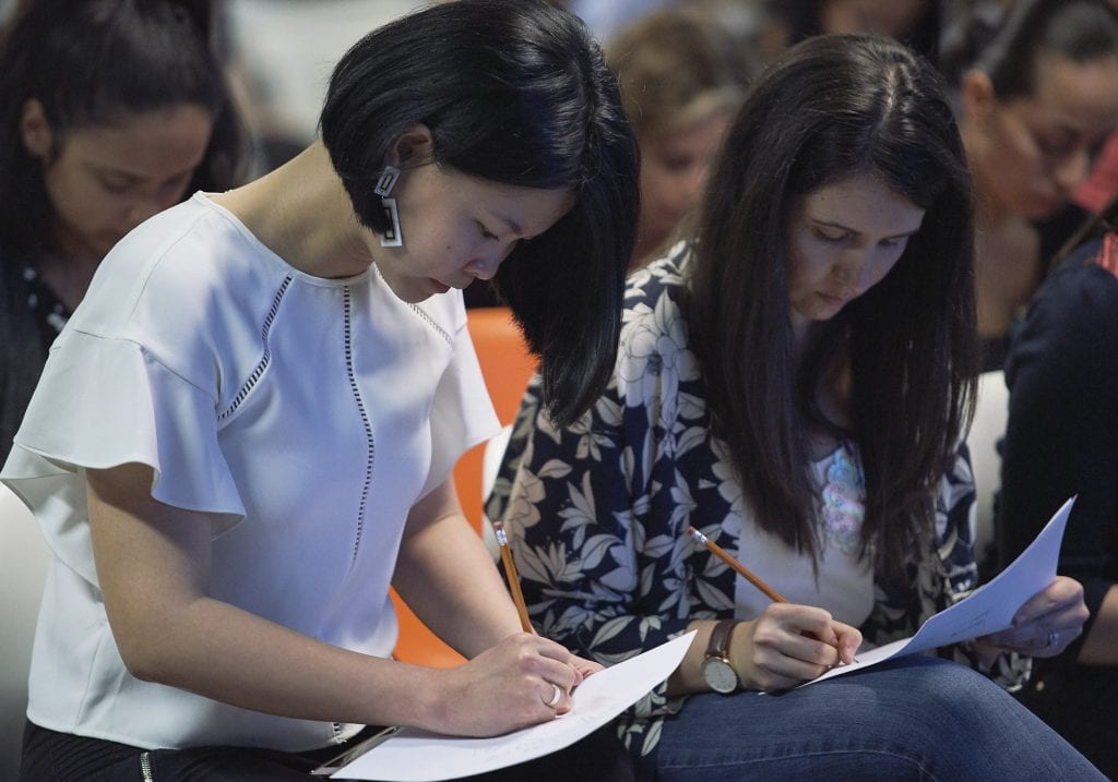 Two women write on paper at a women in male dominated industries event by Vancouver business portrait and branding photographer Angela McConnell