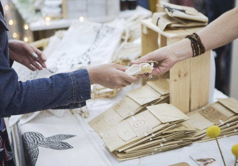 A woman hands her customer a sample product at a makers market by Vancouver business portrait and branding photographer Angela McConnell