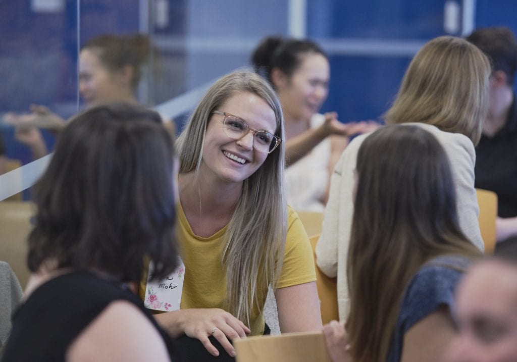 A woman in a yellow top with blonde hair smiles as she talks to another woman at a women in male dominated industries event by Vancouver business portrait and branding photographer Angela McConnell