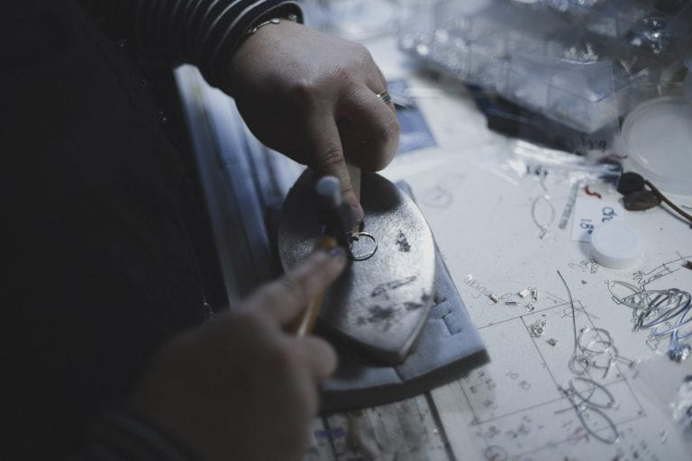Photo of a Salomé from Burfurtart hammering a new piece on a desk with drawn designs and works in progress by Vancouver business portrait and branding photographer Angela McConnell