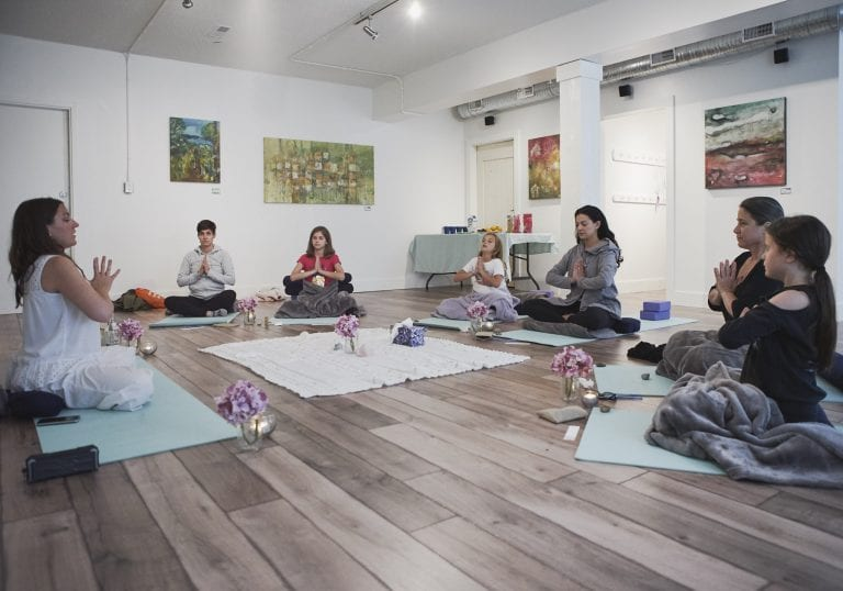 A group of women and their young daughters sit on yoga mats in front of a facilitator during a yoga exercise at a mother and daughter workshop by Vancouver workshop and retreat photographer Angela McC
