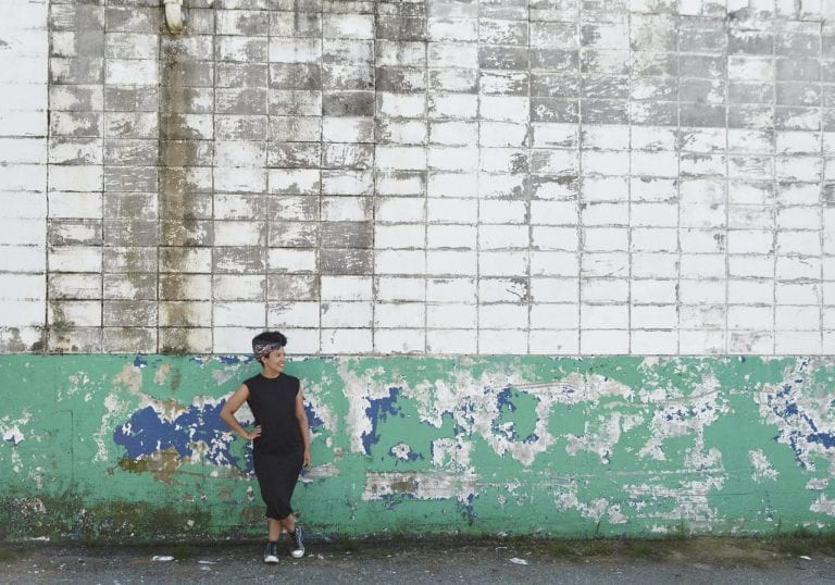 A woman leans against a dilapidated concrete wall during a branding session by Vancouver business portrait and branding photographer Angela McConnell