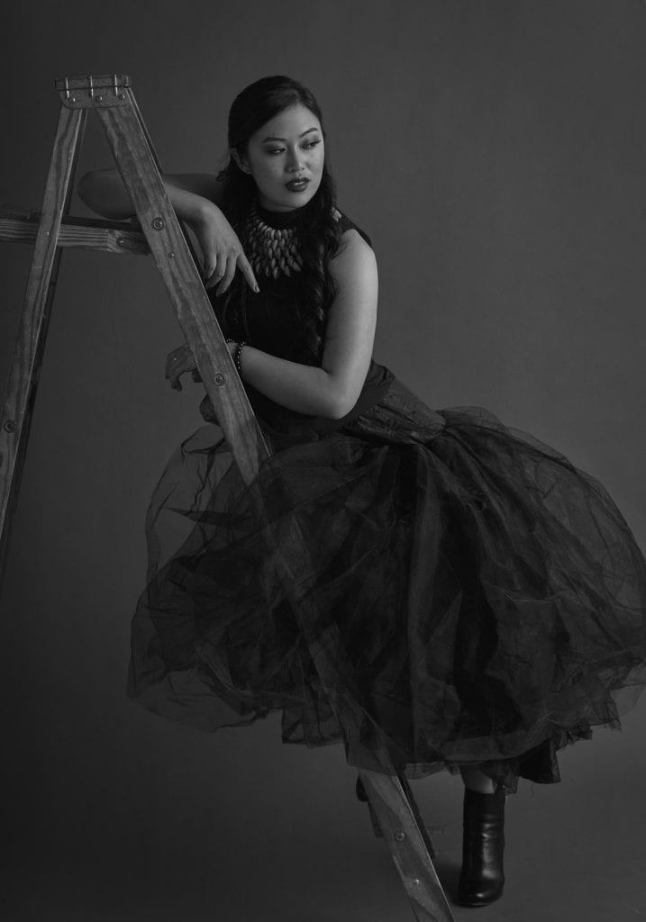 Black and white portrait of a young woman in a large tulle skirt leaning against a wooden ladder by Vancouver contemporary portrait photographer Angela McConnell