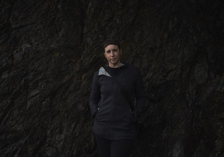 Portrait of a woman standing in front of a stark rock face at Pebbly Beach during a Thanksgiving getaway on Bowen Island