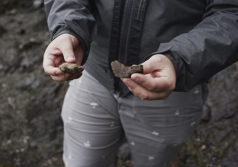 A holds rocks in each hand at Pebbly Beach during a Thanksgiving getaway on Bowen Island