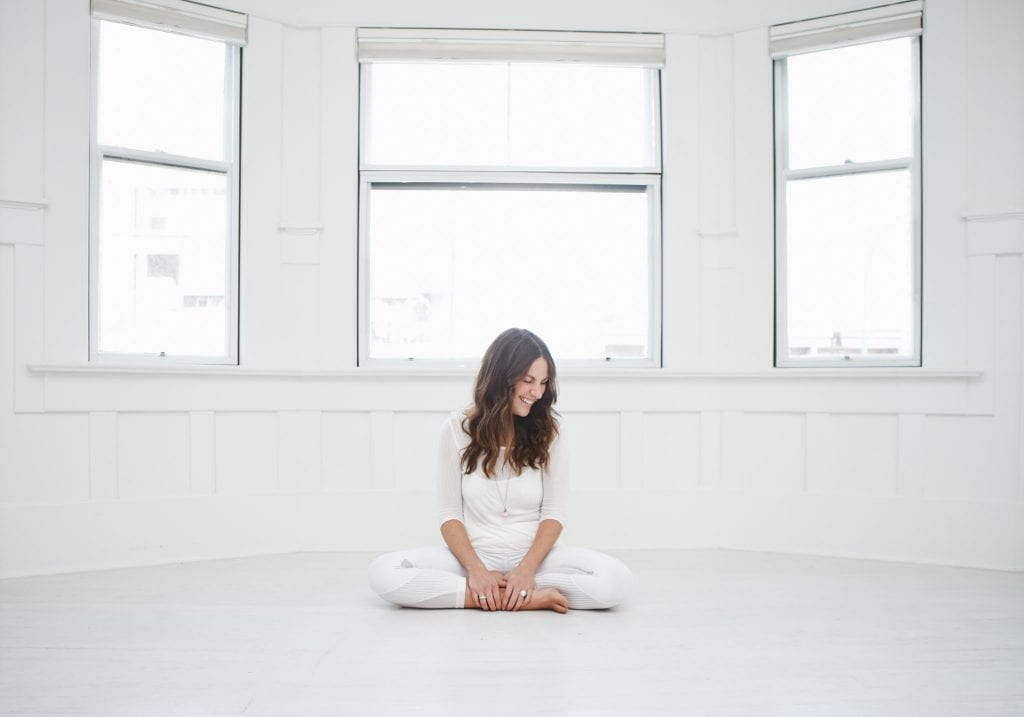 A yoga teacher sits in easy pose in a white room in front of windows at True Nosh Yoga by Vancouver business portrait and branding photographer Angela McConnell