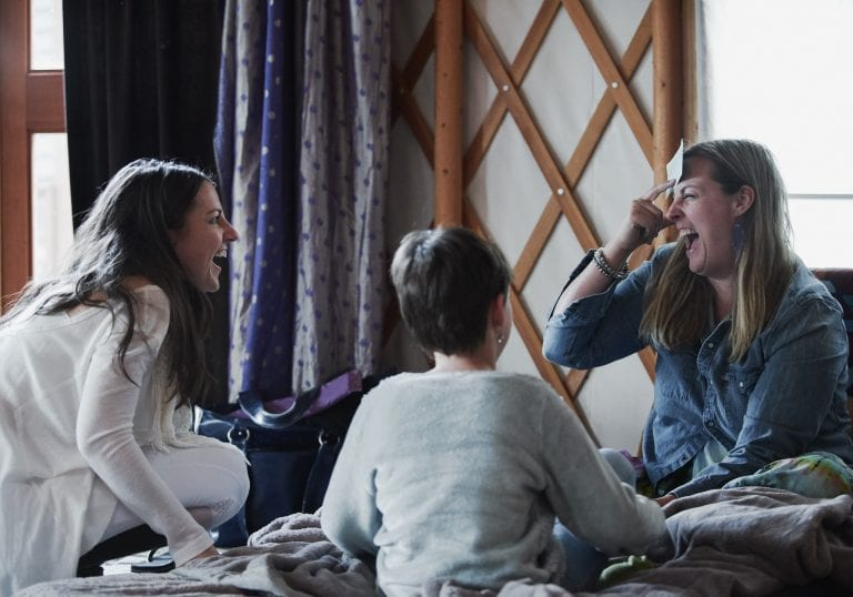 A facilitator and mother laugh together during an exercise at a mother and daughter workshop by Vancouver workshop and retreat photographer Angela McConnell