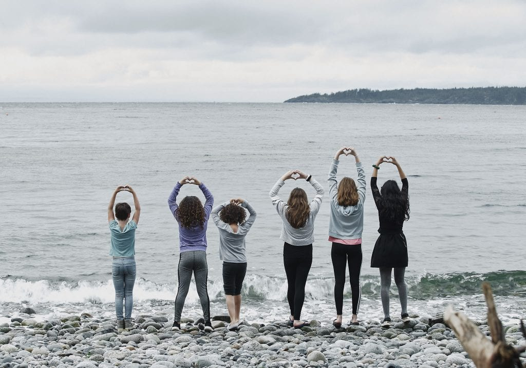 Young girls stand with hand shaped into hearts looking over the water on a pebble beach at Halfmoon Haven in Sechelt BC