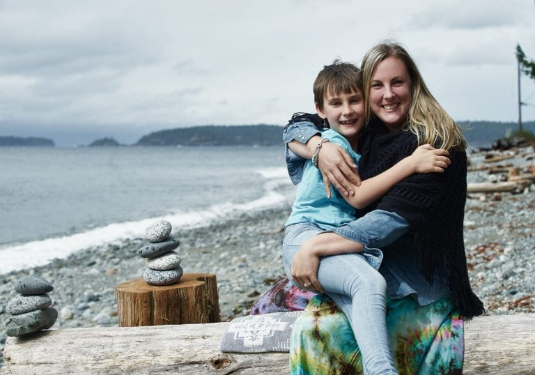 A mother and daughter hug during portraits on a beach at a mother and daughter workshop by Vancouver workshop and retreat photographer Angela McConnell