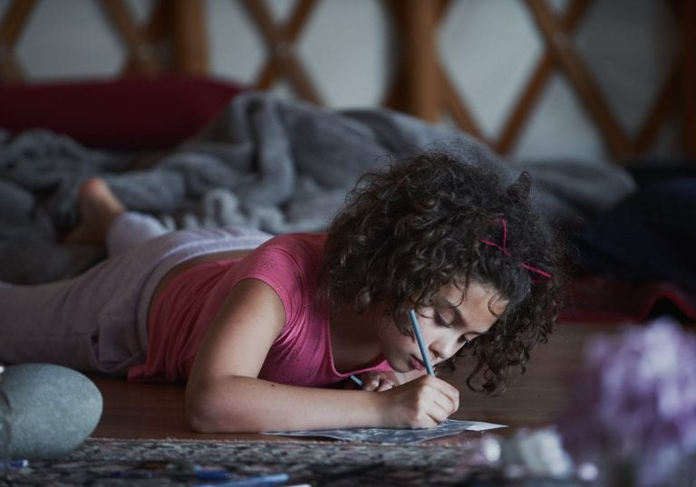 A young girl writes a letter during an exercise at a mother and daughter workshop by Vancouver workshop and retreat photographer Angela McConnell