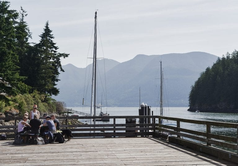 Women sit a table on a pier overlooking the bay at Bowen Island at a courage and bravery workshop by Vancouver workshop and retreat photographer Angela McConnell