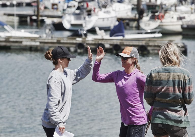A facilitator high fives an attendee at Bowen Island during an exercise at a courage and bravery workshop by Vancouver workshop and retreat photographer Angela McConnell