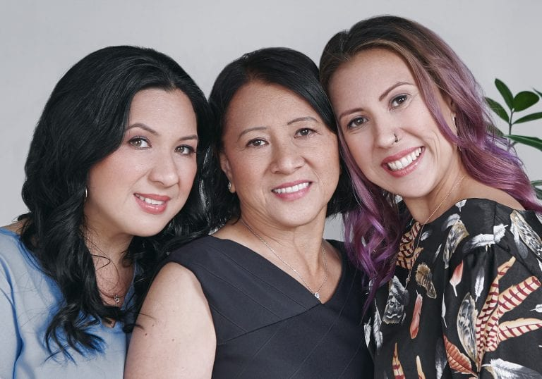 Mother and daughters smile at the camera for a milestone birthday portrait session by Vancouver contemporary portrait photographer Angela McConnell